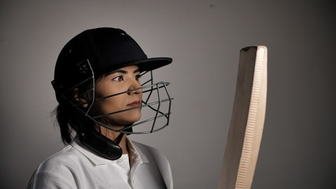 Indian woman cricketer checking her bat before the final match - competitive sports