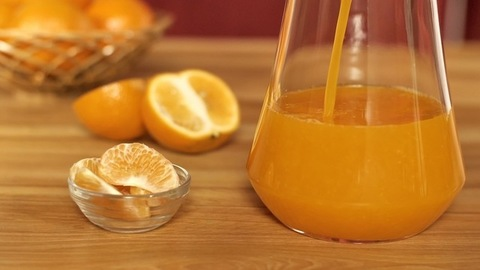 Filling up a glass with freshly squeezed orange juice for a breakfast drink