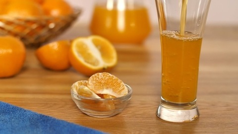 Vitamin-rich orange juice pouring into a transparent glass with slices in a bowl