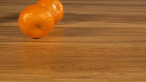 Refreshing juicy oranges rolling down on a wooden table - tropical fruit