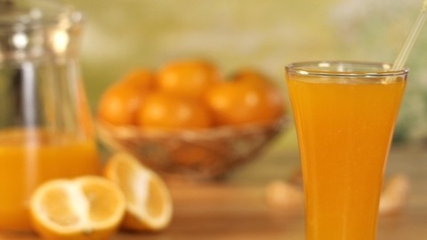 Female hand putting a clear straw in a glass of freshly prepared orange juice