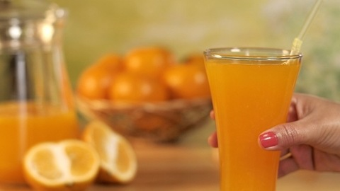 Human hand keeping a transparent glass of fresh orange juice with a straw in it