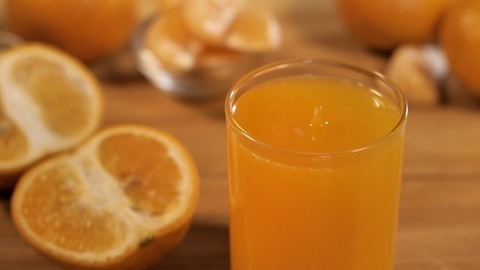 A splash of orange juice dropping in a glass kept on a table - healthy diet
