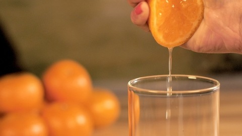 Female's hand squeezing fresh orange juice into a clear glass - healthy diet