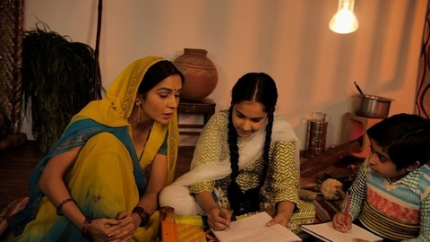 An Indian housewife of a village helping her children to complete their homework