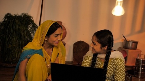 Young mother and daughter of an Indian village using a laptop in their free time