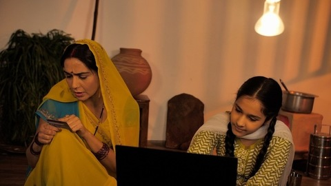 A young village daughter helping her mother in online shopping - Entering credit / debit card details