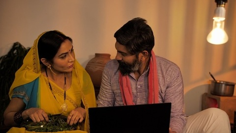 Middle-aged village couple using a laptop at their house - modern technology