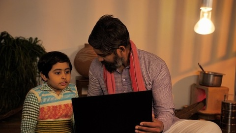 Caring Indian father sitting with his young child teaching him things on a laptop