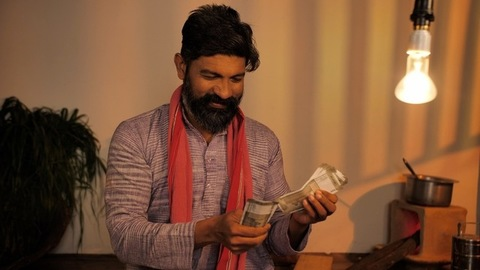 Bearded village man happily counting the banknotes and keeping them in pocket