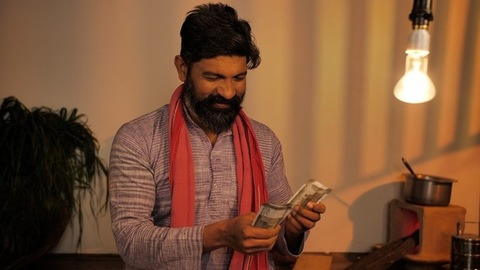 A confident Indian farmer in his early forties with money showing thumbs-up sign