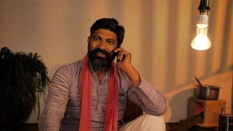 Village scene of a handsome Indian middle-aged farmer busy talking on his smartphone