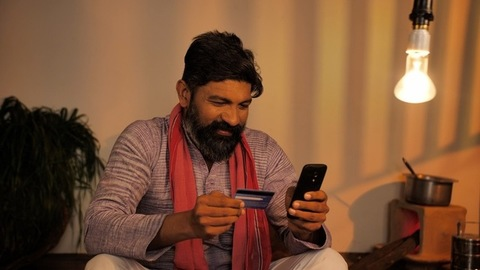 Portrait of Indian farmer putting bank card details in his mobile - modern technology