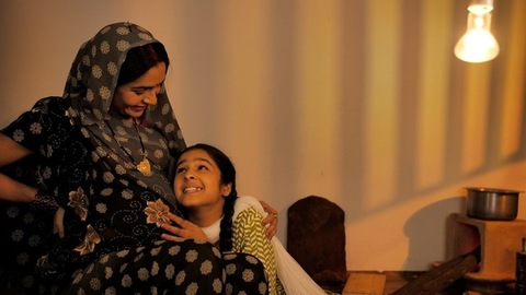 A little village girl hugging her pregnant mother's belly to hear the baby movement