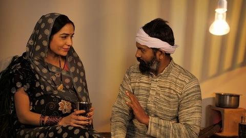 Caring village husband giving medicine to his pregnant wife - prenatal care concept