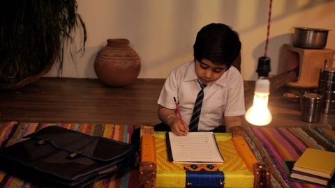 A small school-going child completing his homework sitting alone at home