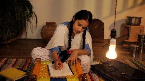 A teenage girl wearing a school uniform, studying in the light of an electric bulb - Indian village home