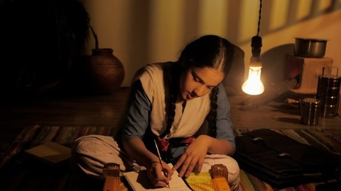 Village student in a school uniform completing homework in a dark village home