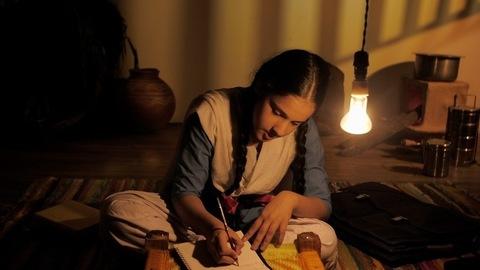 Village student in a school uniform completing homework in a dark village home