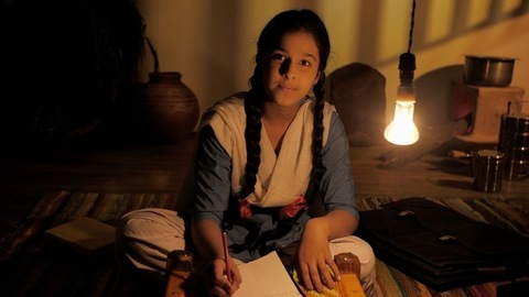 Village girl sitting on a mat taking down notes under the light in the evening - Indian village home