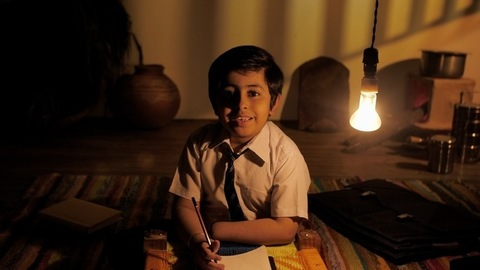 A rural boy from a village completing his homework under an electric bulb