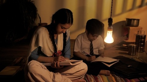 Young boy and girl (Sibling) sitting on the ground and doing homework - Indian village