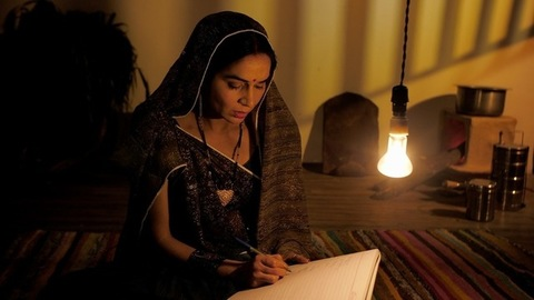 Indian village lady sitting on a mat and studying during the night - adult education