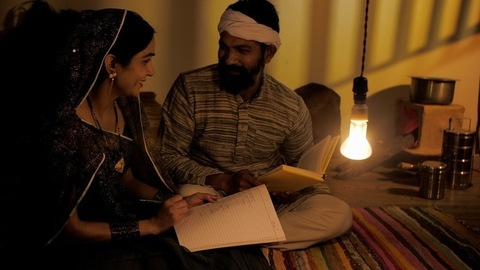 Middle-aged Indian farmer helping his wife to study - adult education
