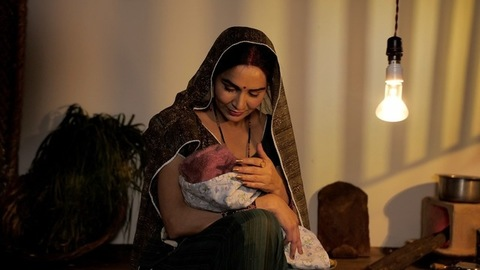 Indian village mother putting her newborn baby to sleep - mother and child moment