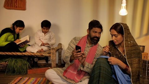 Happy husband showing things on his newly bought smartphone to his wife - Happy family in Indian village