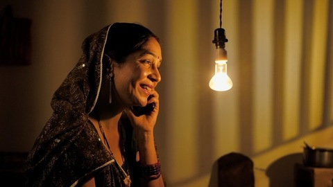 An attractive villager talking on her mobile at home - Independent village woman