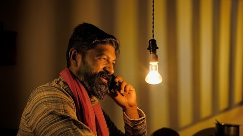 A middle-aged bearded villager talking happily on mobile - modern Indian farmer
