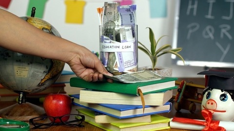 "Indian woman's hand donating money in a glass jar with ""educational loan"" label"