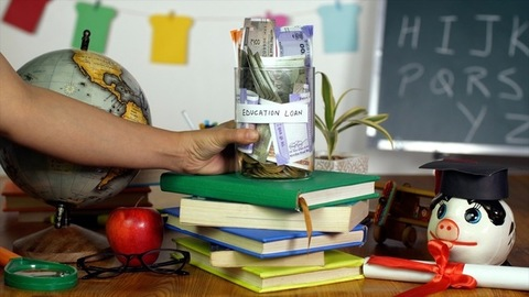 A woman's hand keeping a jar full of money donated for the education of needy