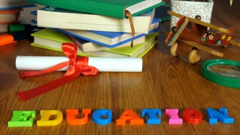 Closeup shot of a teacher's desk with learning materials and the word education