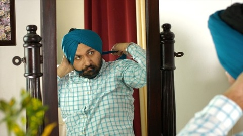 Portrait of an Indian Sardar confidently looking into the mirror while wearing his turban