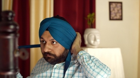 Portrait of a young Punjabi Sardar fixes his blue turban while wearing casual clothes