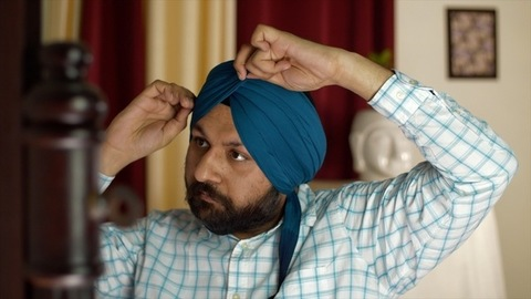 Portrait of a young Punjabi man pleating his blue turban while looking in the mirror