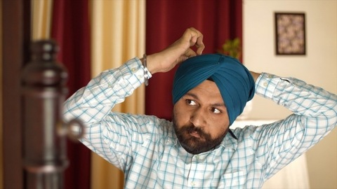 Portrait of a Sikh man fixing turban properly to groom himself before going out