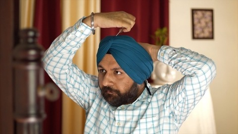 Portrait of a bold Indian Punjabi man fixing his blue turban with a long steel hairpin