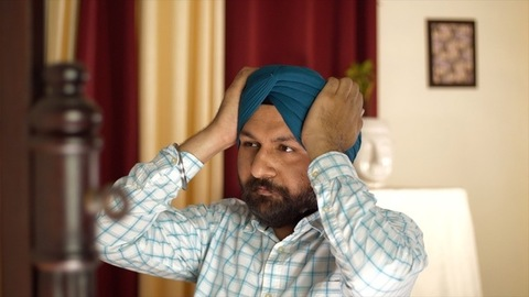 A Sikh gentleman fixing his blue turban while looking confidently to the mirror