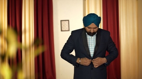 Portrait of an Indian Punjabi gentleman getting ready while wearing a blue turban