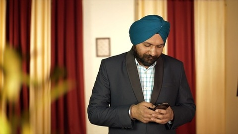 Portrait of a Sikh Indian businessman busy typing message on his smartphone
