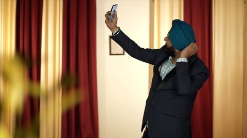 Portrait of a Sikh Indian businessman taking a selfie showing victory sign
