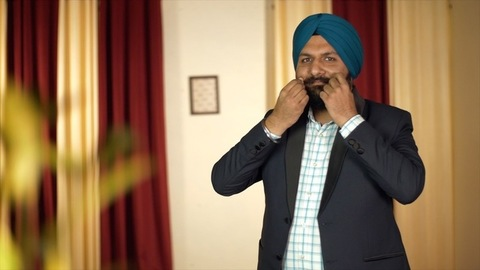 Portrait shot of a happy Sikh man twisting his mustache and folding his hands