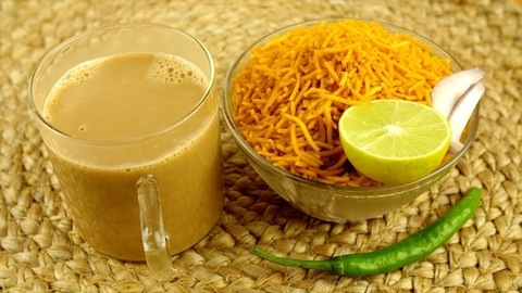 Closeup shot of hands serving a cup of masala chai with a bowl of Aloo Bhujia