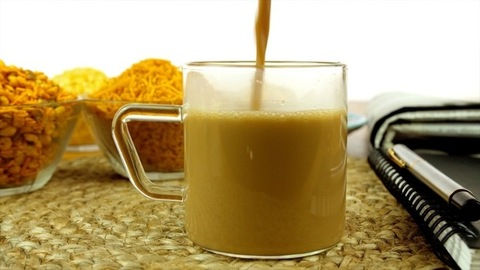 Closeup shot of hands serving hot masala chai in a glass cup with Indian snacks
