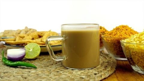 Closeup shot of woman hands placing a transparent cup of Indian masala chai