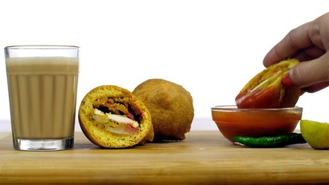 Closeup shot of fried Indian snacks served with ketchup and tea - food concept