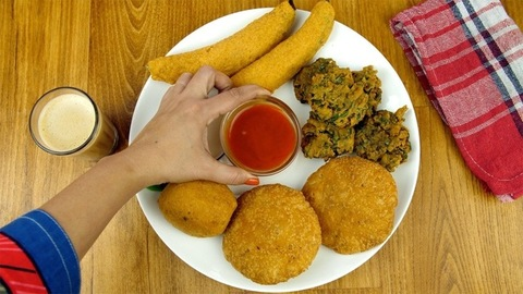 Closeup shot of beautifully placed Indian snacks served with a glass of masala chai
